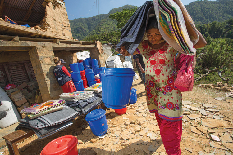 CONTAINING A CRISIS. Catholic Relief Services' staff distribute shelter and hygiene kits in a village in Nepal's Gorkha District.