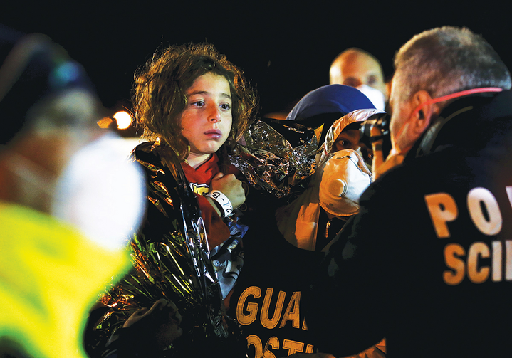 A YOUNG SURVIVOR. Italian police photograph a child after migrants arrived by boat at the Sicilian harbor of Pozzallo on April 19, 2015.