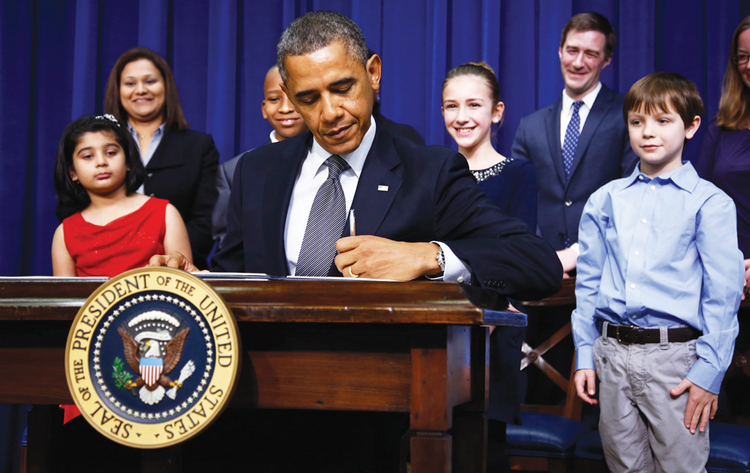 President Barack Obama signs executive orders on Jan. 16.