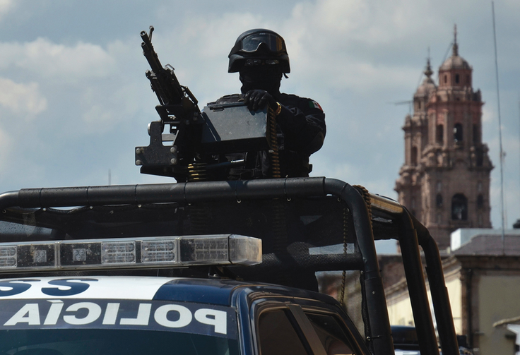 State of Siege: A federal police officer ready for action atop a vehicle in the Mexican state of Michoacan on Oct. 28