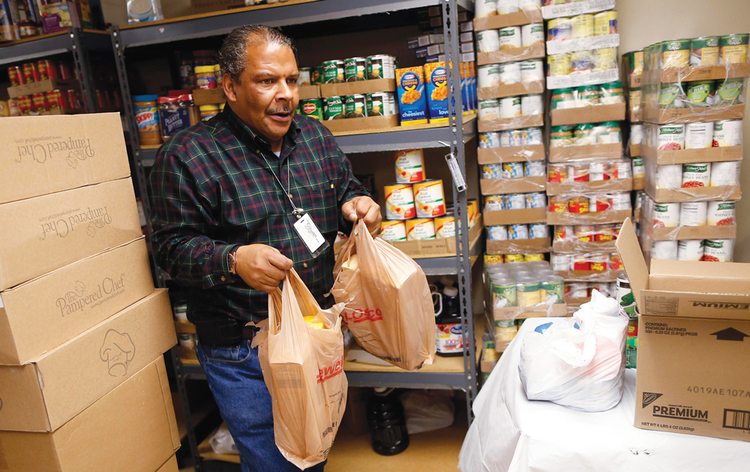 New Costumers: A volunteer prepares packages at a Catholic Charities food pantry in Chicago.
