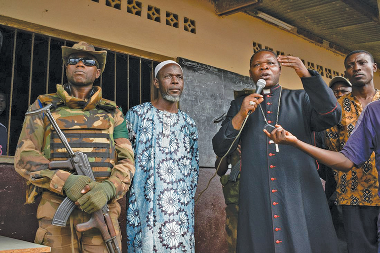 Peace Offensive: Archbishop Dieudonné Nzapalainga and Imam Omar Kobine Layama tour a church on the outskirts of Bangui in mid-December in an effort to promote tolerance and reconciliation.