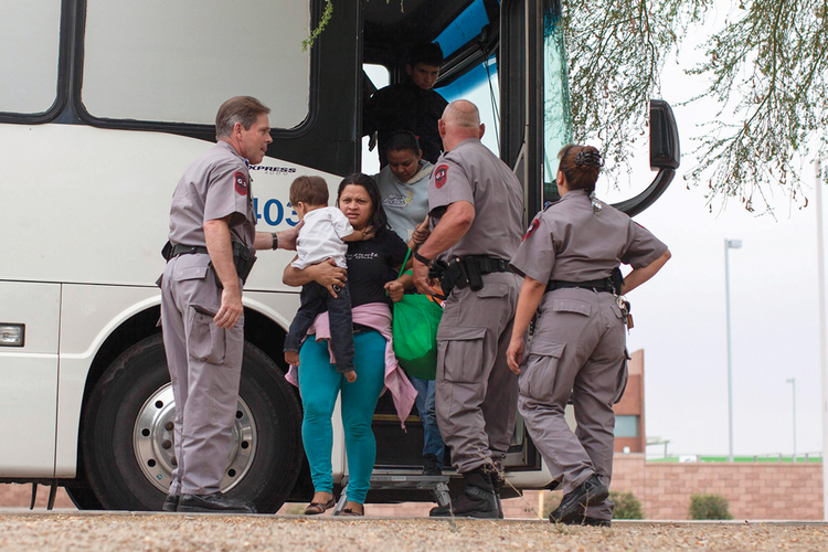 CROSSING GUARDS. Migrants, mostly women and children, disembark from a U.S. Immigration and Customs Enforcement bus in Phoenix.