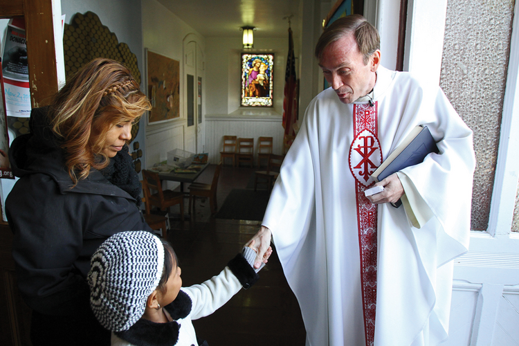 FOND FAREWELL. Mark Hallinan, S.J., greets parishioners at St. Mary of the Assumption Church in Staten Island on Nov. 2, one of more than 30 churches that will close by August 2015.
