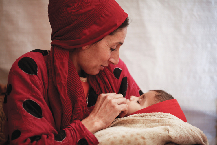 MOTHER AND CHILD. Souad Mohamed, a Syrian refugee, with her her baby inside a tent in Lebanon's  Bekaa Valley, December 2013.