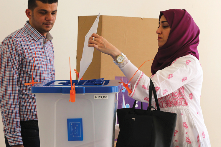 An Iraqi woman living in Jordan casts a ballot at a polling station in Amman.