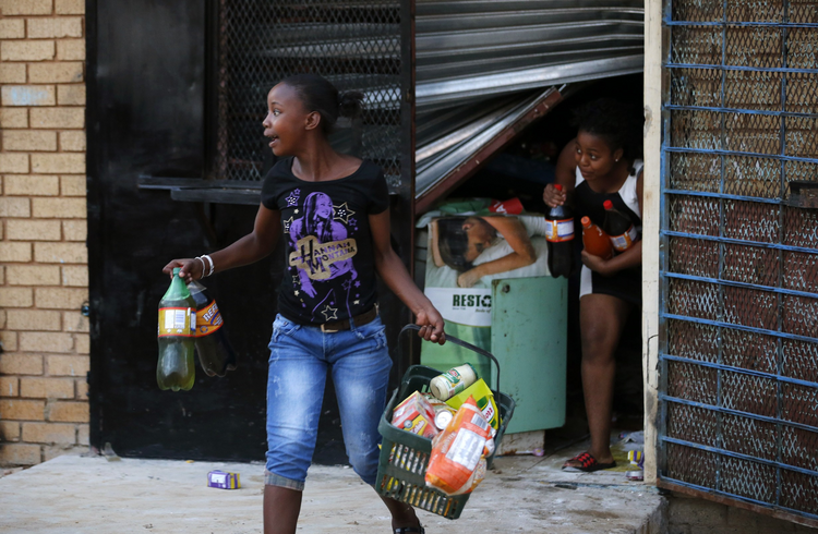 Locals run with items from a shop in Soweto, South Africa, Jan. 22. Local media reported that violence broke out Jan. 19 after a 14-year-old South African was allegedly shot dead by a foreign shop owner. (CNS photo/Siphiwe Sibeko, Reuters)
