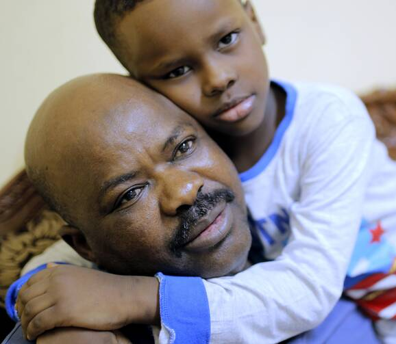 Sudanese activist Tayeb Ibrahim, who had worked to expose Sudanese abuses in the volatile South Kordofan province and hopes to see family living in the U.S. state of Iowa, is hugged by his son Mohammed during an interview with The Associated Press in Cairo, Egypt, on June 28, 2017. (AP Photo/Amr Nabil)
