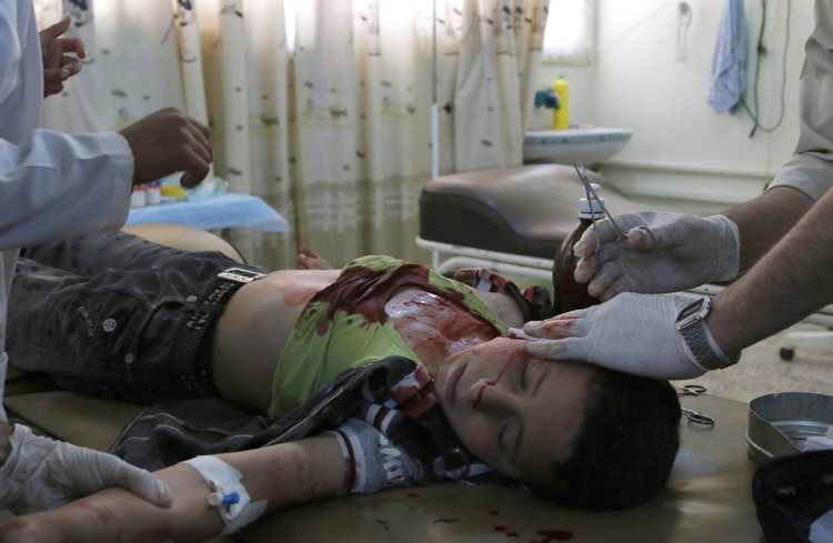 A medic treats a boy who was injured after what activists said was an airstrike by forces loyal to Syrian President Bashar Assad at a hospital in Idlib, Syria, on May 15.