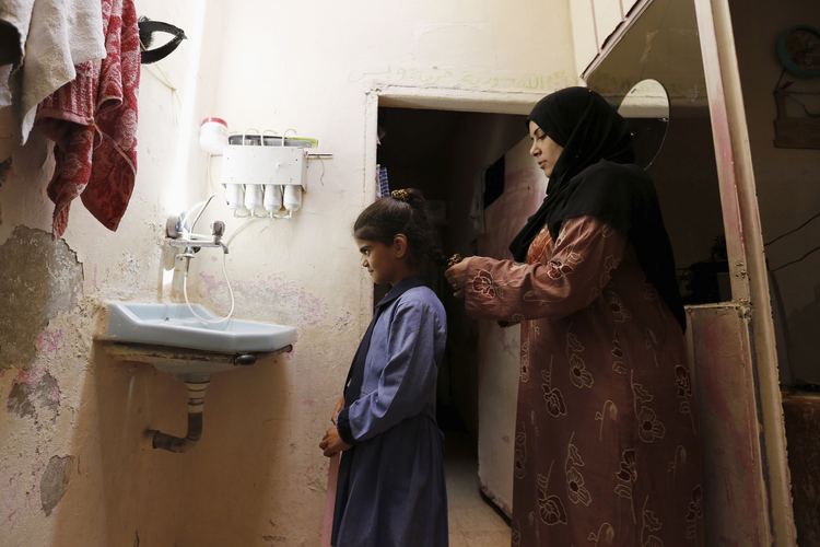 Rana, a 31-year-old a Syrian refugee living in Jordan, adjusts her 8-year-old daughter's hair at their home at a refugee camp in Amman. World Refugee Day is June 20.
