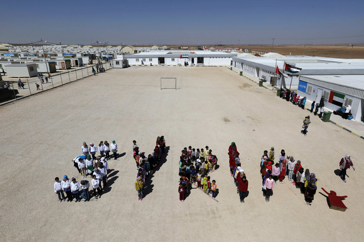 "Syrian refugee children at the Mrajeeb Al Fhood refugee camp in Jordan form the word ""Syria"" during an event to commemorate four years of the Syrian conflict, March 15. (CNS photo/Muhammad Hamed, Reuters)"