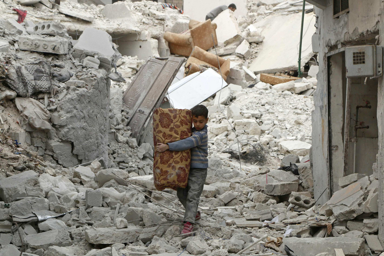 A boy walks on the rubble of damaged buildings in Aleppo, Syria in November 2014. (CNS photo/Hosam Katan, Reuters)