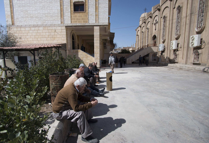 Displaced Assyrians, who fled from the villages around Tel Tamr, Syria, gather in March outside the Assyrian Church in Hassakeh as they wait for news about abductees remaining in Islamic State hands. (CNS photo/Rodi Said, Reuters)