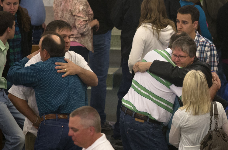 Residents embrace after service at Catholic church four days after deadly fertilizer plant explosion in Texas.