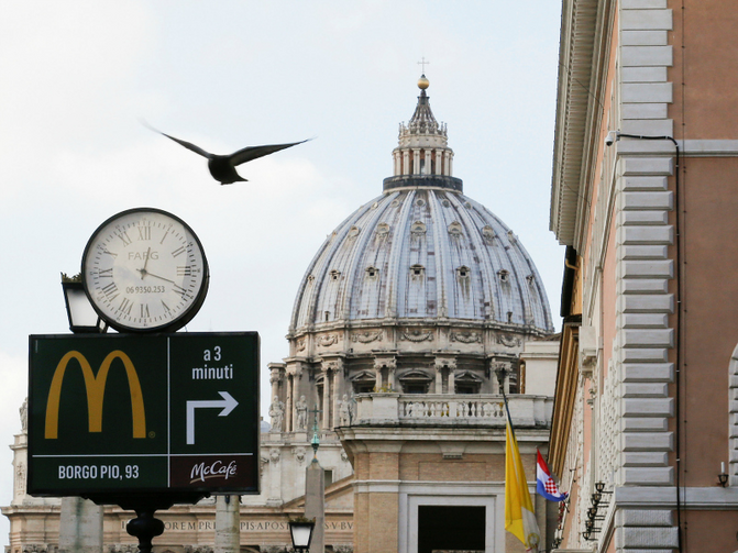 A sign in front of St. Peter's Basilica points to the newest McDonald's restaurant in Rome, next to the Vatican. Jan. 3, 2017. Photo courtesy of Reuters/Alessandro Bianchi