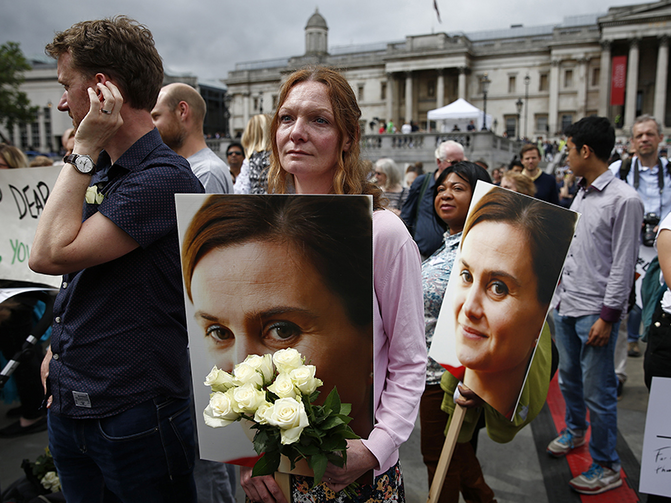 woman holds a placard and white roses during a special service for slain Labour Party MP Jo Cox, at Trafalgar Square in London, on June 22, 2016. Photo courtesy of REUTERS/Peter Nicholls