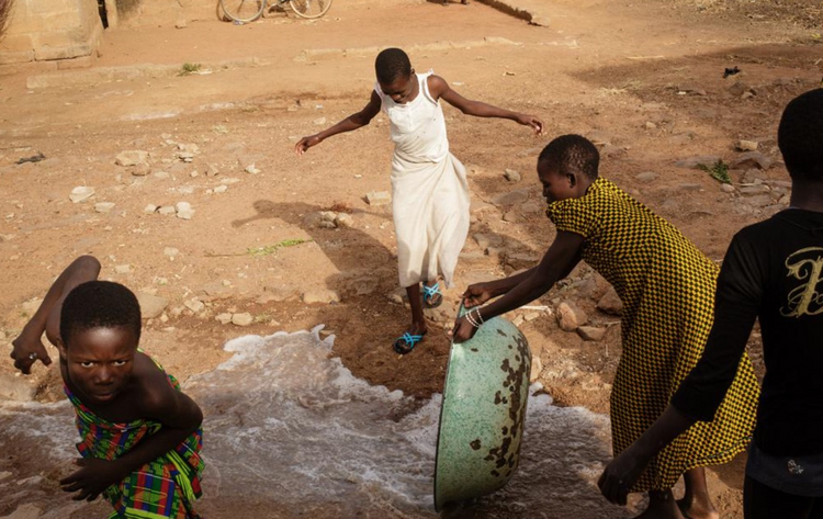 Water is thrown in the street in front of a Vivre dans l'Espérance (Living in Hope) orphanage after a bath in Togo. Photo by Julien Pebrel / Myop
