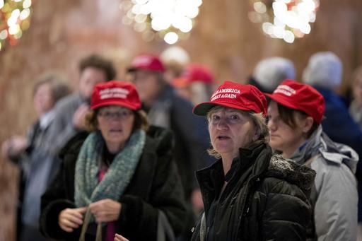 "Visitors to the lobby of Trump Tower wear ""Make America Great Again"" hats, Monday, Dec. 5, 2016, in New York (AP Photo/Andrew Harnik)."