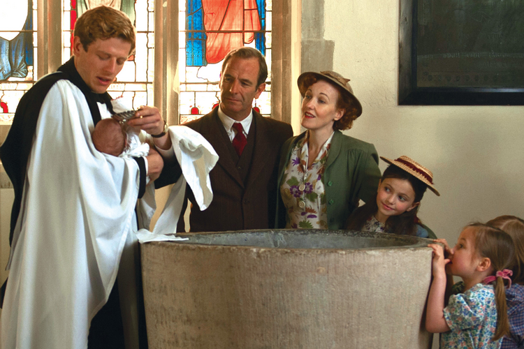 "A MAN OF MANY TALENTS. Sidney Chambers baptizes the son of his crime-solving partner, Inspector Geordie Keating, in ""Grantchester."""