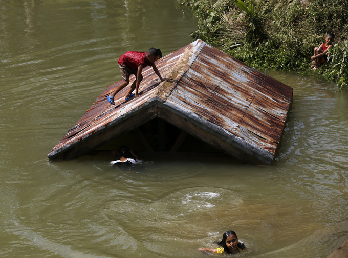 Children swim in a swollen river on Samar Island, Philippines, Dec. 8. Typhoon Hagupit left at least 21 people dead and forced more than a million people into shelters (CNS photo/Francis R. Malasig, EPA).