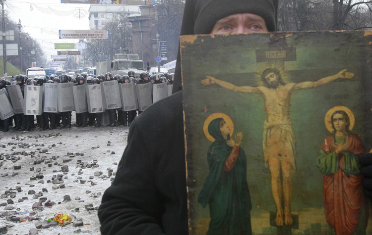 A priest stands between police and protestors in Kiev.