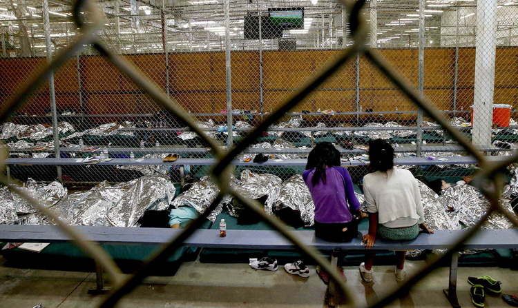 Two young girls watch a World Cup soccer match in a holding area where hundreds of mostly Central American immigrant children are being processed in Nogales, Az., on June 18.