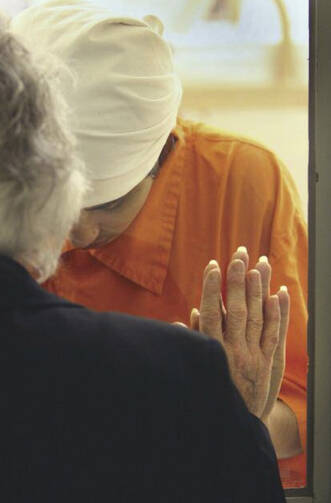 Solitary Prayer: A prison chaplain prays with a Catholic inmate in Cambridge Springs, Pa.