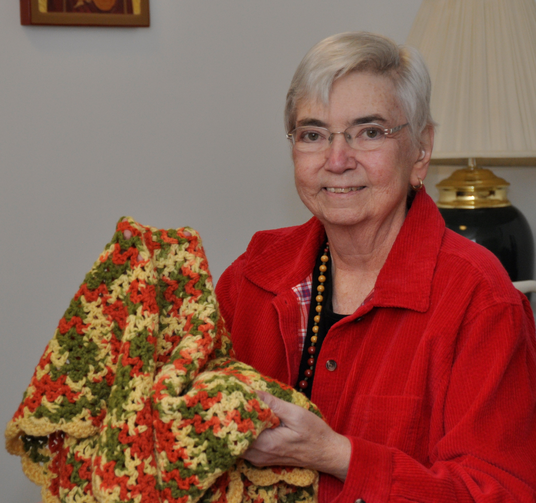 Mercy Sister Mary Ann Walsh takes comfort in a prayer shawl given to her by a former colleague in this 2014 photo taken at the Mercy Motherhouse in Albany, N.Y. (CNS photo/courtesy Catherine Walsh, Northeast Communications for the Sisters of Mercy)