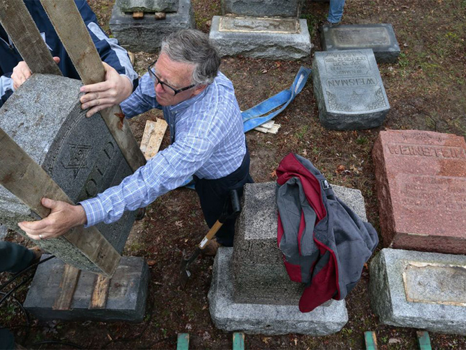 Philip Weiss of Rosenbloom Monument Co. reset headstones at Chesed Shel Emeth Cemetery in University City on Feb. 21, 2017, where almost 200 gravestones were vandalized over the weekend (photo: Robert Cohen/St. Louis Post-Dispatch).