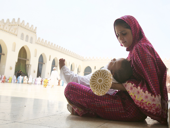 A Shiite woman calms her crying child as she waits with other Shiite Muslims from south Asia to greet their spiritual leader in Cairo, Egypt, on June 12, 2010. (Photo courtesy of Reuters/Asmaa Waguih)