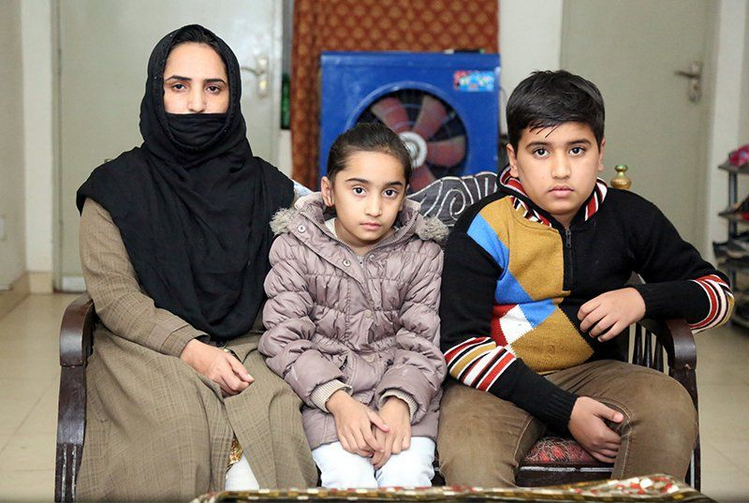 Ruby Tabbasum, left, the wife of an Ahmadi man who was killed in a hate crime in 2016, with her daughter, Huzaifa Ahmad, 9, and son, Amtul Mateen, 12, at their home in Rabwah, Pakistan. RNS photo by Naila Inayat
