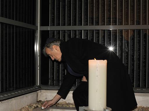 In this Dec. 10, 2009 file photo, Elie Wiesel lights a candle for Holocaust victims on a memorial wall, which identifies tens of thousands of Hungarian Holocaust victims, in the Holocaust Memorial Center in Budapest, Hungary (AP Photo/Bela Szandelszky).