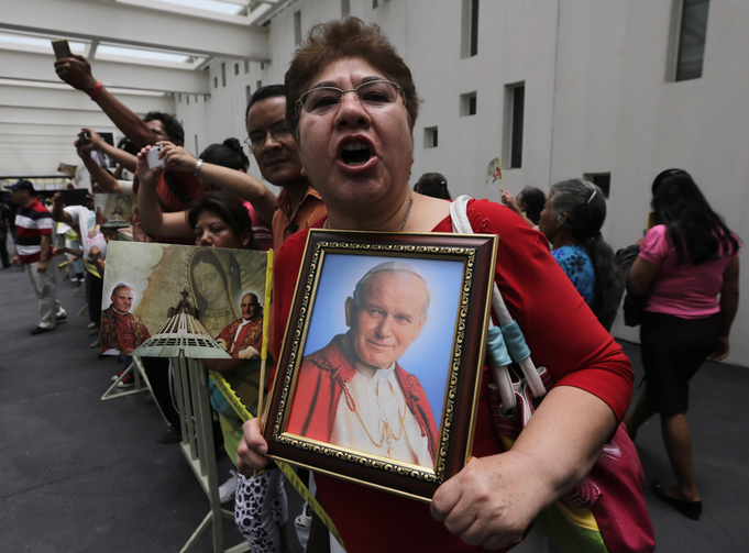 A woman holds up a portrait of St. John Paul II after a Mass at the Basilica of Guadalupe in Mexico City April 27 to celebrate the canonizations of Sts. John Paul and John XXIII. (CNS photo/Henry Romero, Reuters)
