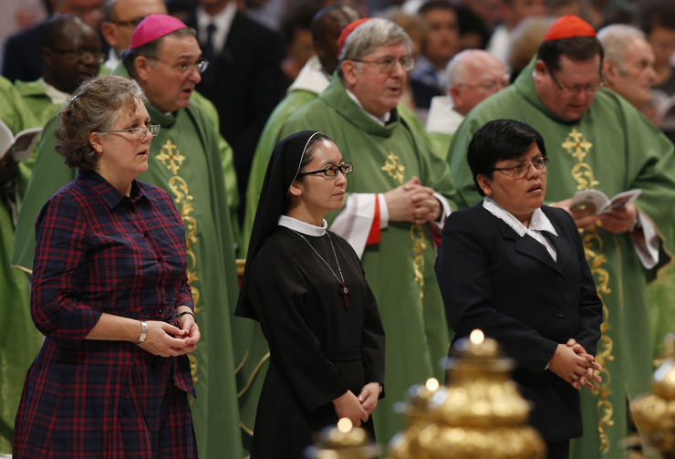 Women wait to read intentions as Pope Francis celebrates Mass of Thanksgiving for canonization of two Canadian saints.