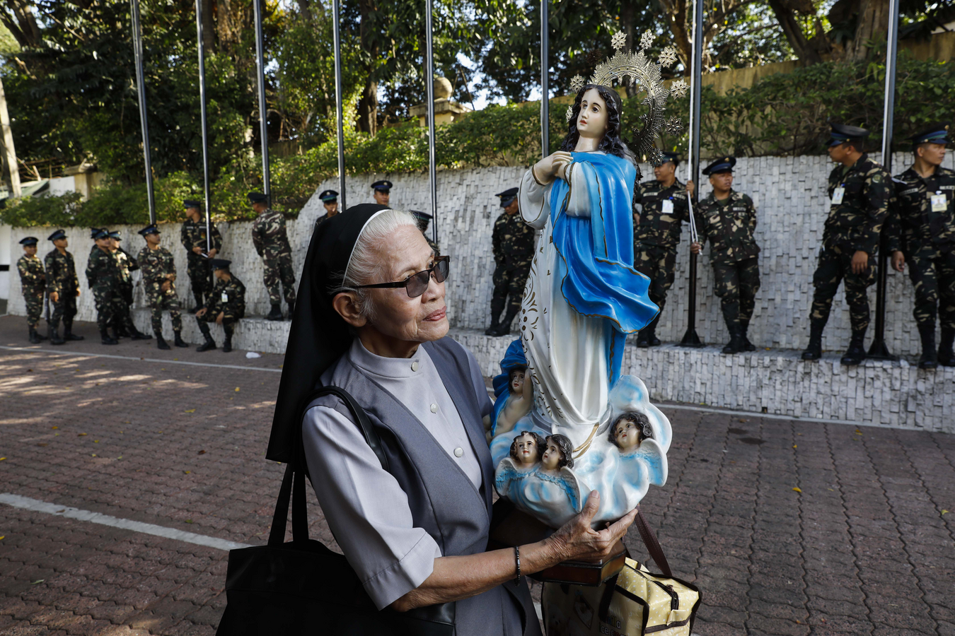 A nun holds a statue of Mary Feb. 23 as soldiers prepare for a flag-raising rehearsal for ceremonies marking the February 1986 anniversary of the People Power Revolution in Manila, Philippines. The nonviolent revolution led to the toppling of President Ferdinand Marcos and the restoration of the country's democracy. (CNS photo/Rolex Dela Pena, EPA)