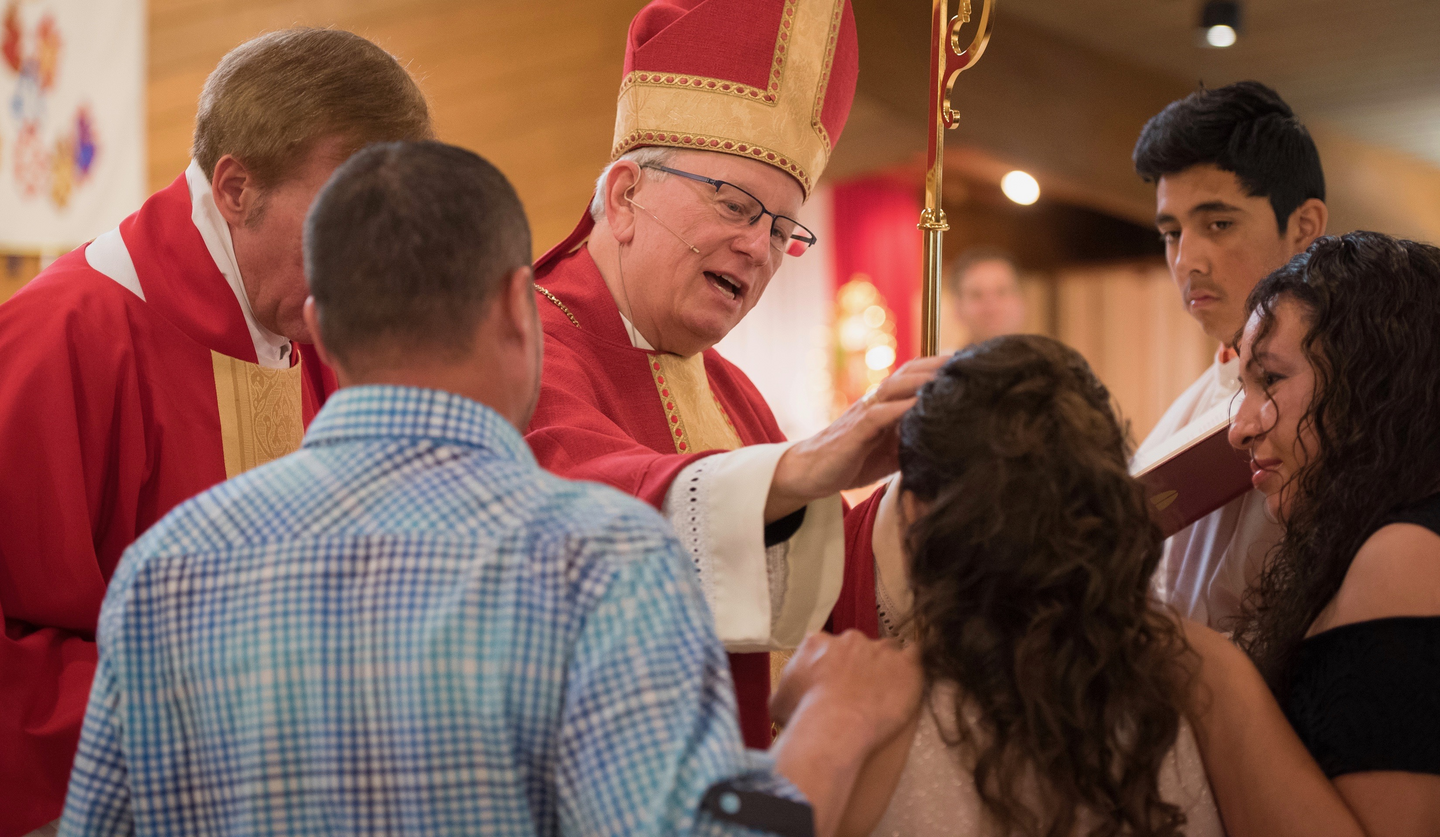 Bishop David L. Ricken of Green Bay, Wis., uses chrism oil to trace a cross on the forehead of a girl completing the sacrament of confirmation in 2017. (CNS photo/Sam Lucero/The Compass)