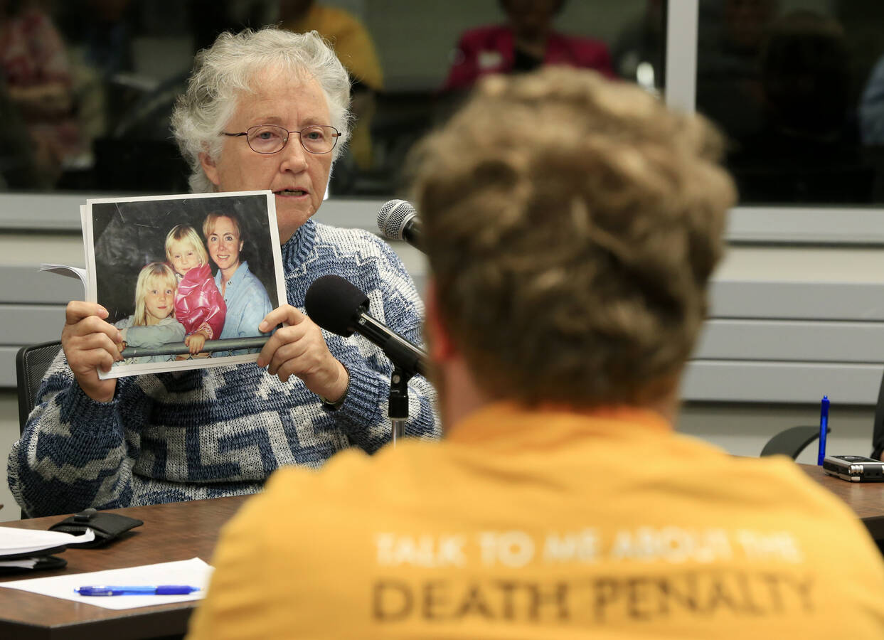 Vivian Tuttle holds a photo of her daughter Yvonne, who was murdered during a 2002 bank robbery in Norfolk, Neb., as she testifies in favor of the death penalty at a public hearing in Omaha, Neb. in October 2016 (AP Photo/Nati Harnik, file).