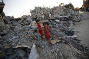 Sisters walk among the rubble of destroyed home in Gaza Strip. (CNS photo/Mohammed Saber, EPA)
