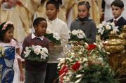Children carry flowers to place at a figurine of the baby Jesus as Pope Francis celebrates Christmas Eve Mass in St. Peter's Basilica at the Vatican on Dec. 24. (CNS photo/Paul Haring)