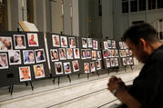 A man prays on June 15, 2016, in front of photographs of victims of the mass shooting at an L.G.B.T. nightclub in Orlando, Fla., during a vigil at a nearby church. The mass shooting was one of the hate crimes discussed on July 16 at a hearing held by the Helsinki Commission. (CNS photo/Jim Young, Reuters)