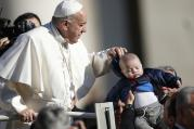 Pope Francis adjusts the hoodie of a baby during his general audience in St. Peter's Square at the Vatican on March 29. (CNS photo/Paul Haring)