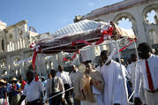 A priest carries a monstrance in a Corpus Christi procession on June 15, 2017, as people pass the ruins of the the Cathedral of Our Lady of the Assumption in Port-au-Prince, Haiti. (CNS photo/Andres Martinez Casares, Reuters)