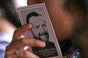 A woman holds a booklet with a picture of Father Stanley Rother