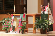 Father Joe Townsend, pastor of St. Benedict Parish in Broken Arrow, Okla., bows before the altar and an image of Father Stanley Rother during a Sept. 22 vespers and vigil