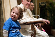 A young girl sitting next to Pope Francis smiles during an audience with Special Olympics athletes participating in the Unified Football tournament, at the Vatican Oct. 13. (CNS photo/L'Osservatore Romano)