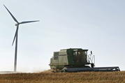 A combine harvests wheat near a wind turbine close to Lincoln, Kan., in this 2008 file photo. Two religious communities were pleased that two Midwest utilities recently agreed to publish climate risk assessment reports in alignment with the Paris climate accord. (CNS photo/Larry W. Smith, EPA) See SHAREHOLDERS-CLIMATE March 2, 2018.