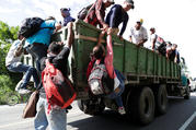 Honduran migrants climb on a truck Oct. 23 in Chiquimula, Guatemala, as they travel with other Central Americans in a caravan heading to the United States. (CNS photo/Luis Echeverria, Reuters)