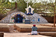 A displaced Christian woman prays in front of a grotto with a statue of Mary in Kaya, Burkina Faso, May 16, 2019. Bishop Laurent Dabire of Dori, president of the bishops' conference of Burkina Faso and Niger, has urged international action to stop the massacre of Christians by foreign-backed Islamist groups. (CNS photo/Anne Mimault, Reuters)