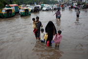 A family wades through a flooded street during heavy rains in New Delhi, India, Aug. 6, 2019. Catholic churches and other institutions opened their doors to people stranded in Mumbai and surrounding areas because transportation routes were blocked by high water and debris. (CNS photo/Adnan Abidi, Reuters)