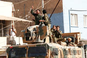 "Members of Syrian National Army, known as the Free Syrian Army, react as they drive on top of an armored vehicle Oct. 11, 2019, in the Turkish border town of Ceylanpinar. Dozens of advocacy organizations participating in the International Religious Freedom Roundtable called on U.S. President Donald Trump ""not to abandon Christians, Yazidis and Kurds"" in the Syrian border region that Turkey is bombing. (CNS photo/Murad Sezer, Reuters)"